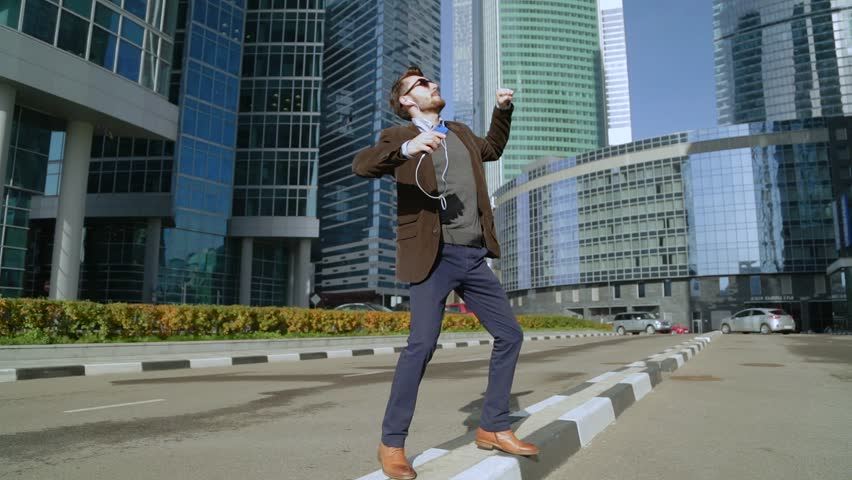 Handsome man listening to music in smartphone headphones and dancing near skyscrapers | Shutterstock HD Video #21840850