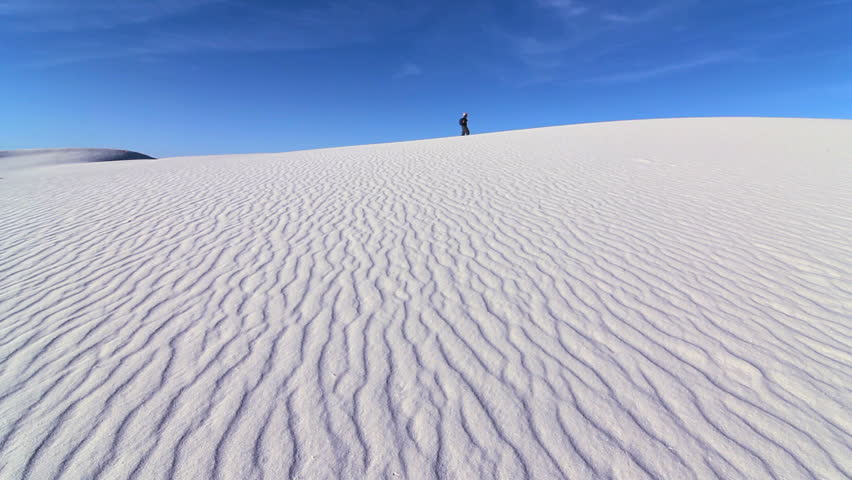 Lone hiker walks along ridge of textured dune in White Sands National Monument, New Mexico. 1080p