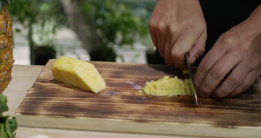Male hands chopping pineapple on the wooden cutting board