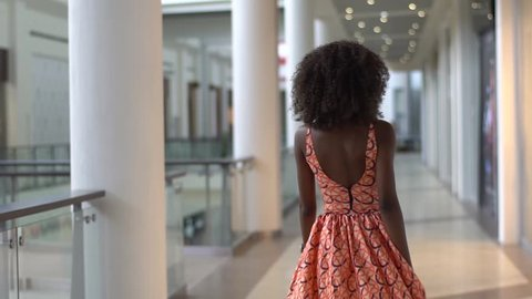Young sexy afro-american girl walking in the bright orange dress in the trade centre, turning and looking back