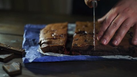 Man slicing cake on wooden table. Prepared chocolate cake pieces on kitchen. Chef cutting chocolate cake. Brownie cake slices