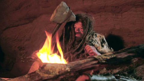 Prehistoric caveman looks at the fire and his spear in his cave