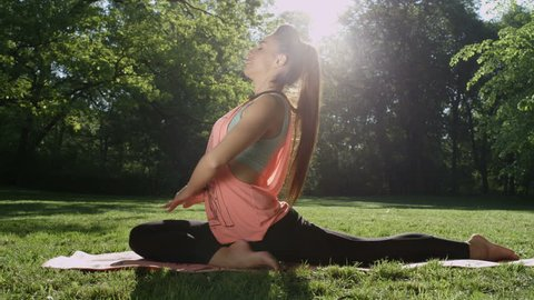 Young woman stretching in sunny park. Fitness girl training outdoors in landscape of nature. Fit female working out. Concept of sport and healthy lifestyle.