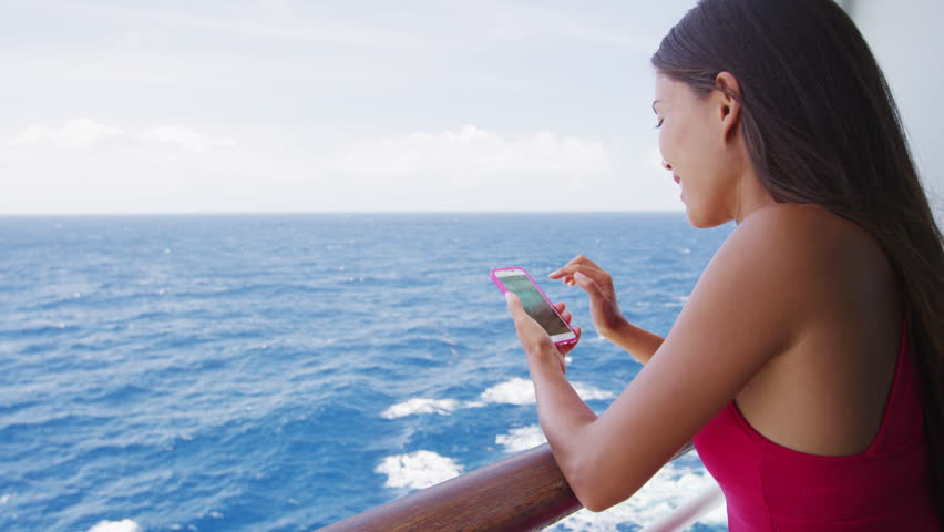 Smart phone close up - woman using smartphone app on cruise ship vacation travel at sea.