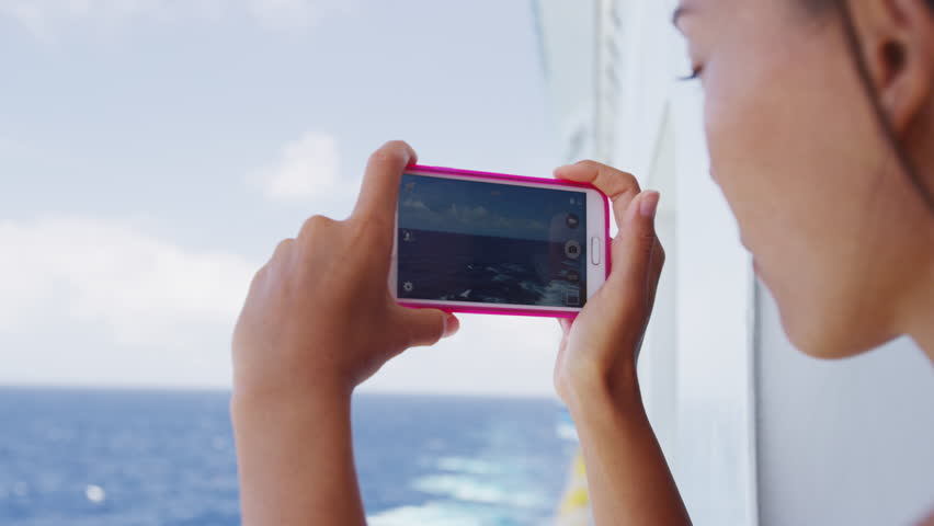 Cruise ship vacation girl taking photo with smart phone camera enjoying travel at sea. Woman using smartphone to take picture of ocean. Woman on luxury cruise liner boat.
