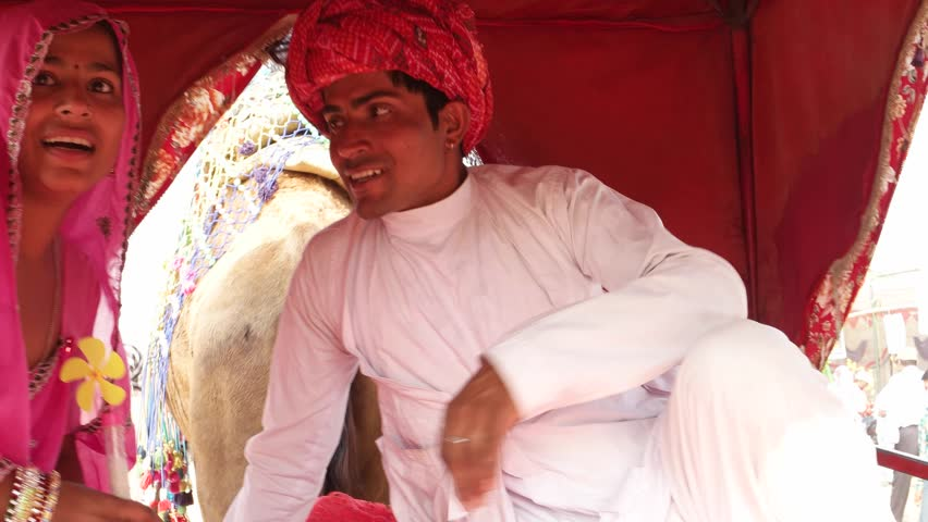 6d0ac02145 Handheld shot of Indian couple enjoying a camel ride in a caravan at  Pushkar Fair, Rajasthan, India