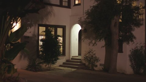 Magic Hour night slight tight from sidewalk window arched entry 2 story stucco Spanish style small apartment duplex, brown trim, tiled roof, palm, lights on,