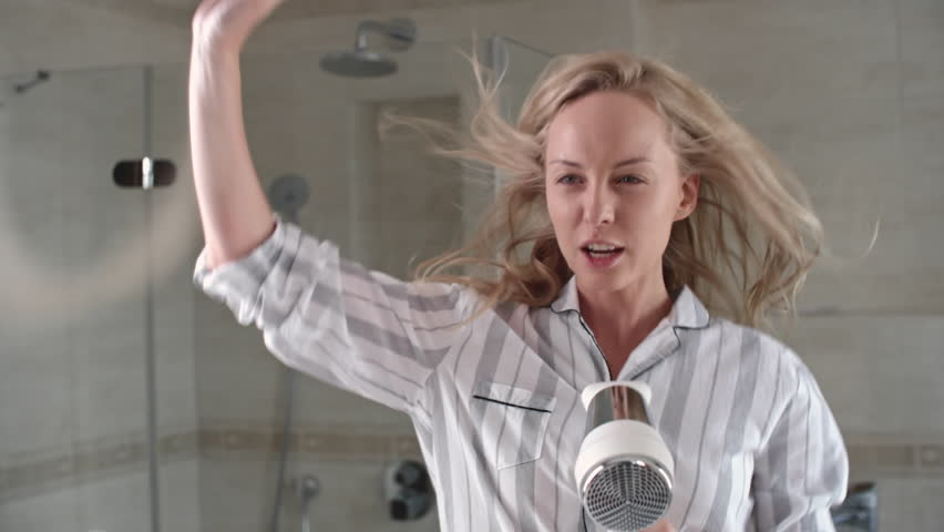 Pretty blonde girl dancing and singing with hair dryer in bathroom