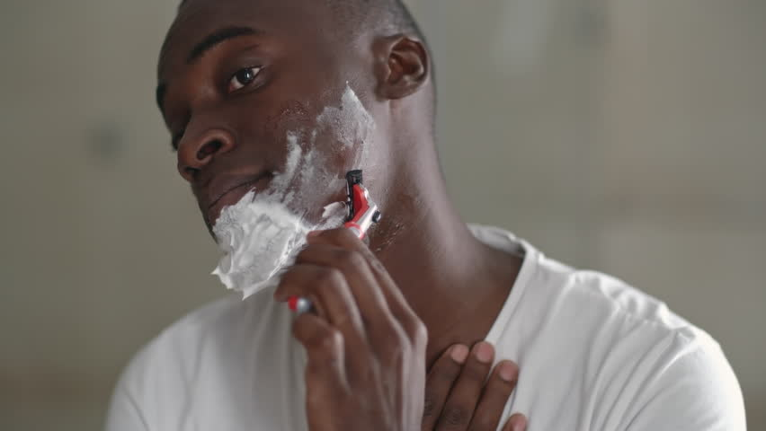 African man with foam on his face using razor to shave off beard