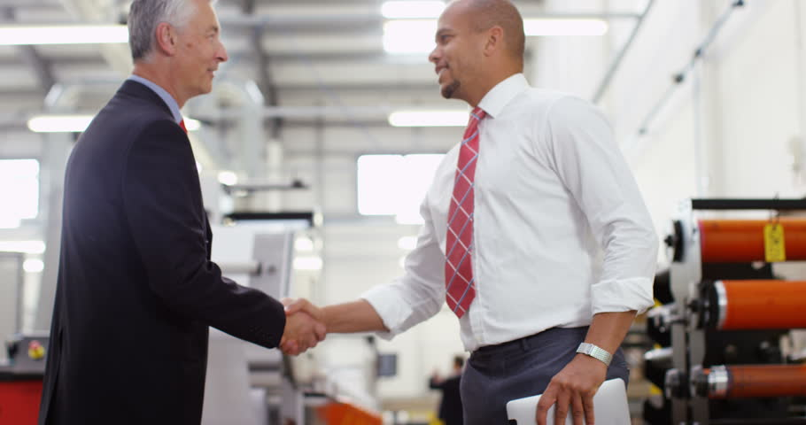4K Businessmen greet each other & shake hands on the factory floor, looking at computer tablet & discussing operations