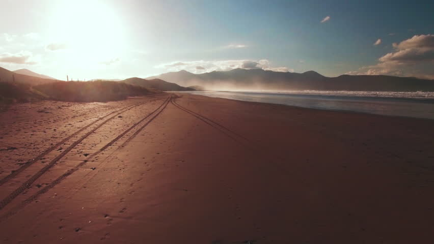 Aerial drone footage of beach and ocean at sunset. Low flying tracking shot of beach with waves in the background. | Shutterstock HD Video #21993850