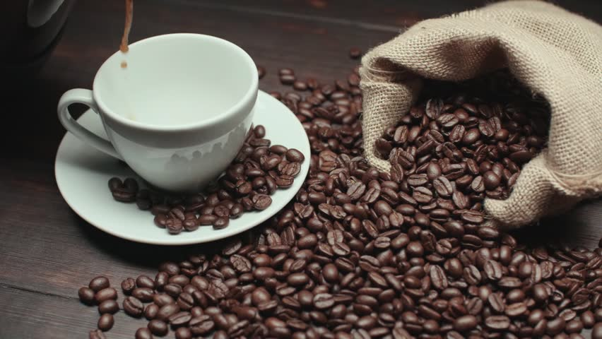 pouring a Cup of hot coffee and roasted coffee beans on the table, slow motion