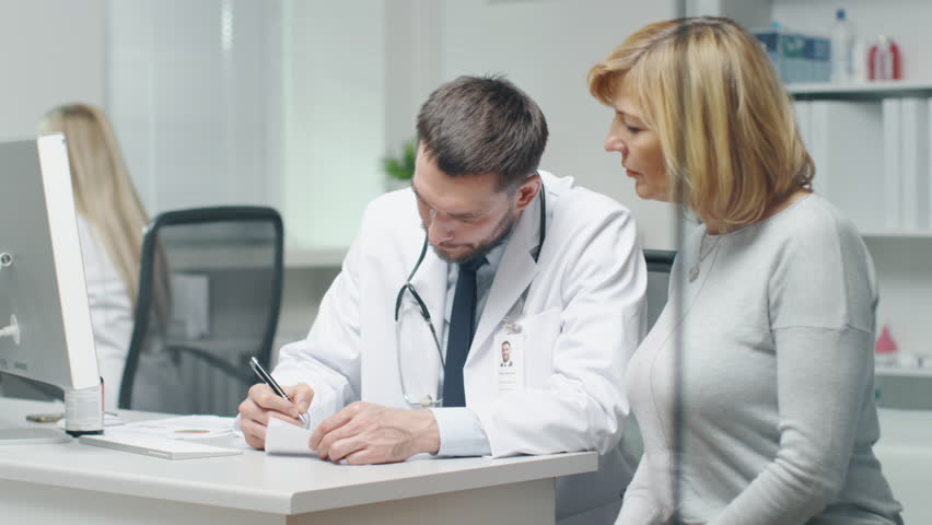 Doctor Writes Prescription to his Mid Adult Female Patient. They Talk and Smile.