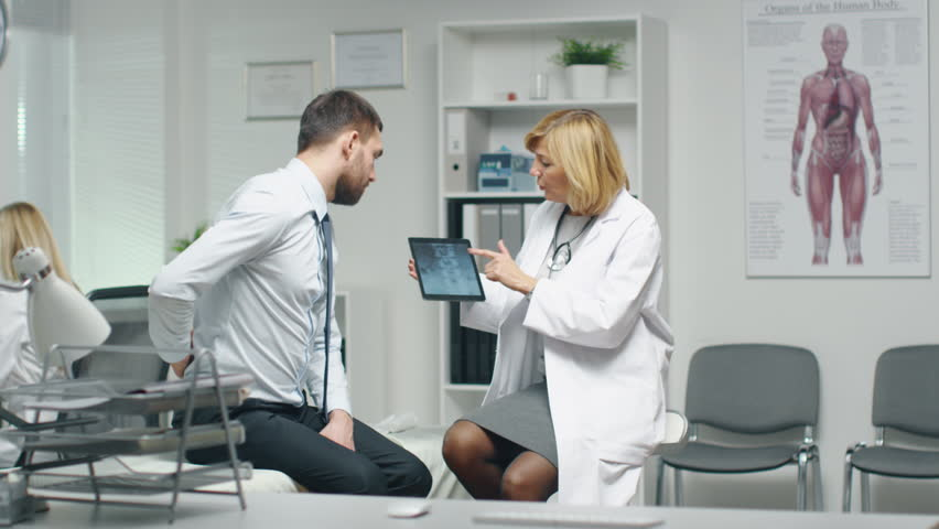 Mid Adult Female Doctor Consults Young Man About His Back Pain. Doctor Shows Him Tablet Computer With His Spine X-Ray.