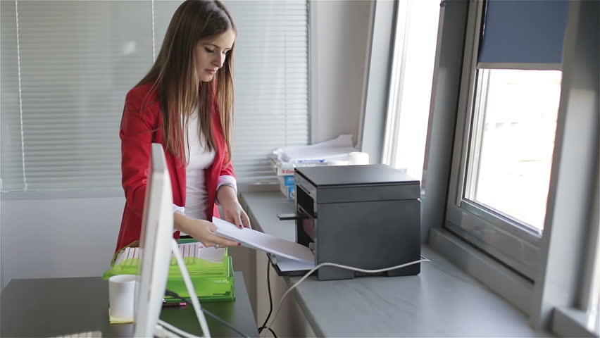 Young beautiful woman making copies of files in the copy machine. Assistant manager working at the office.