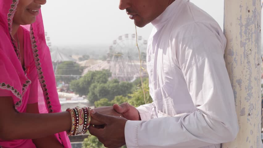 Romantic couple dating at a secret location with view of a carnival in the backdrop in pink sari, red turban and white kurta