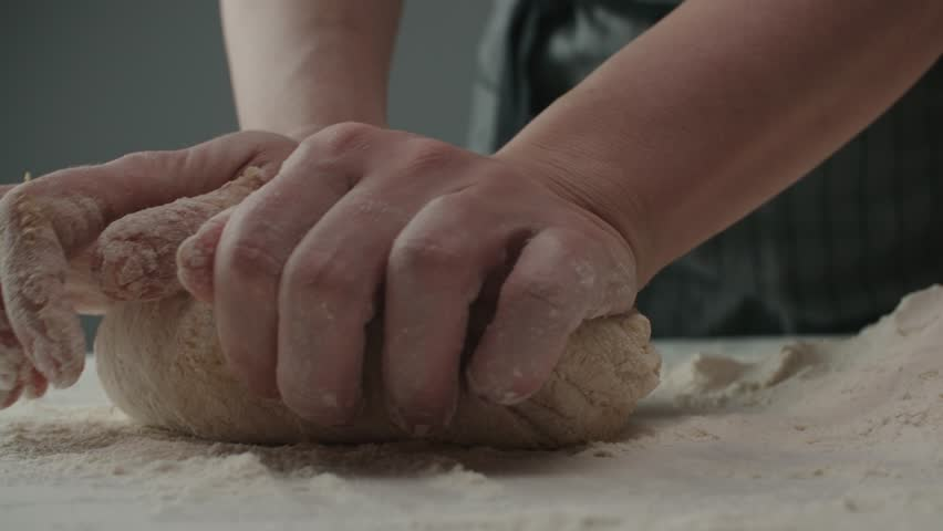 4? Baker kneading dough in flour on table, slow motion