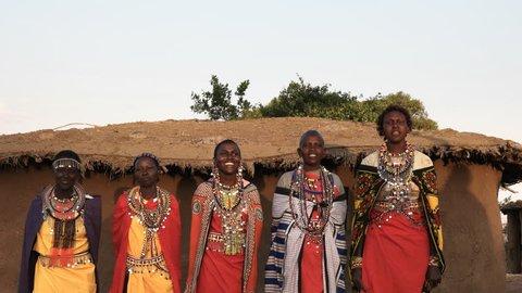 wide shot of five maasai women in traditional dress singing and dancing in a village near maasai mara, kenya