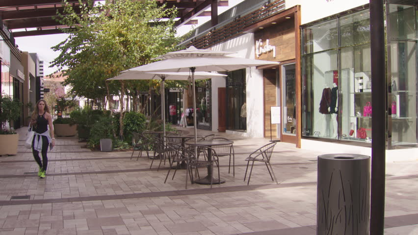 Day hold upscale outdoor shopping plaza mall very few people, breezy pans left bit (Nov 2014) | Shutterstock HD Video #22056790
