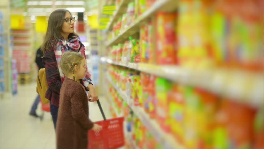 Woman and Girl Choosing Products in Shopping Mall. Mom and Daughter After Puting Some Goods in Red Basket Walk Along Shelves in the Supermarket | Shutterstock HD Video #22084261