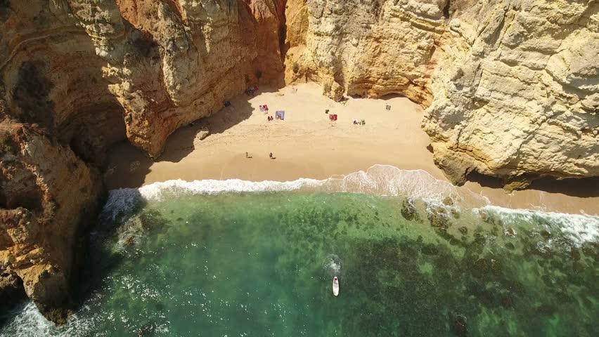 Aerial. Small beach with tourists, in the bay Ponta de Piedade.
