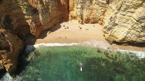 Aerial. Small beach with tourists, in the bay Ponta de Piedade.