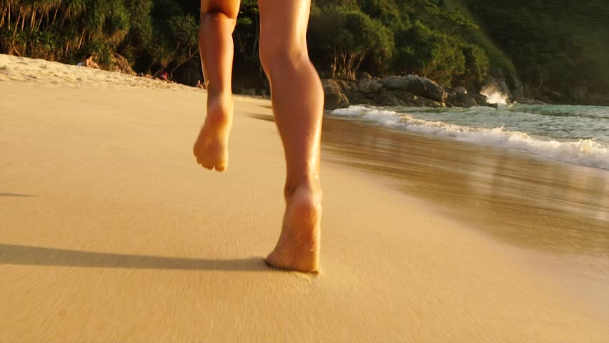 Feet little girls run barefoot on the golden sand beach. Slow motion.