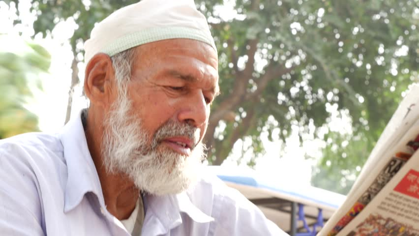 Bearded senior muslim reading newspaper