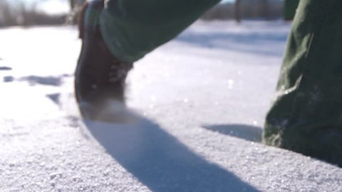 Close-up of man's feet walking on the mountains in the snow. Slow-motion filming