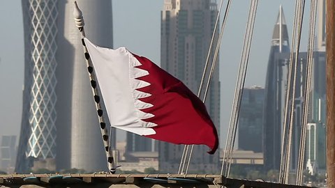 flag of Qatar sea side on a dhow cruise boat, with Doha towers in the background