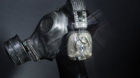 a gas mask covered in sparkling crystals spins on a mannequin head. this is a special handmade item from our studio. how to survive the apocalypse in bling bling style