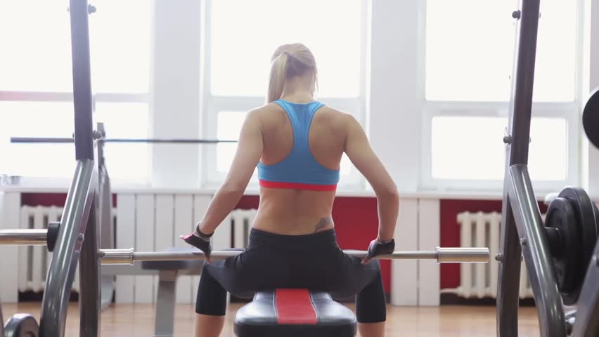 1b5d68e548823 Young adult girl doing bench barbell in gym. Woman with muscular body doing  lifting exercise. Fit women do fitness