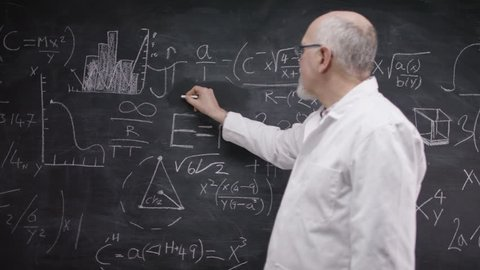 4K Portrait of academic man writing math formulas on blackboard