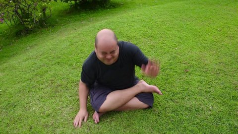 A fat bald head Asian Thai man is angry like a spoil child and then pounding wriggly tantrum aggressively on green grass in HD quality. Psychiatrist therapy is needed.