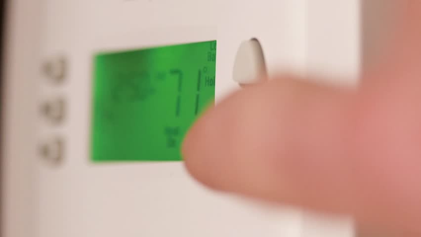 Digital thermostat used for heating and cooling - Energy expense and finance concept