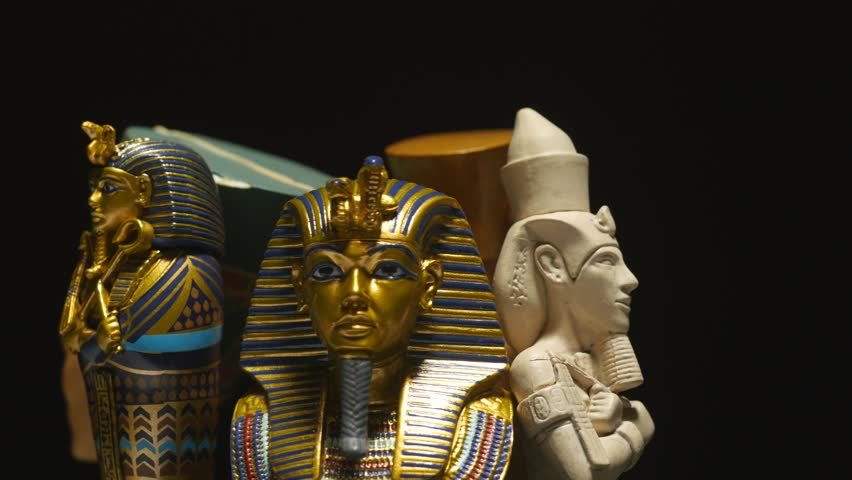 many Egyptian sculptures on a stand. Dark black background.