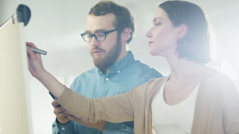 Young Man and a Woman Discuss Working Process on a Whiteboard. Man Holds Smartphone. Woman Draws on a Whiteboard. Shot on RED Cinema Camera in 4K (UHD).