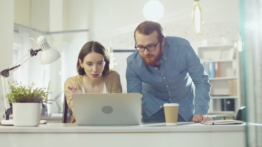 Portrait Shot of a Man and a Woman Discussing Work Looking Streight at the Camera. They are in the Brightly Lit Modern Office. Shot on RED Cinema Camera in 4K (UHD).   Shutterstock HD Video #22195306