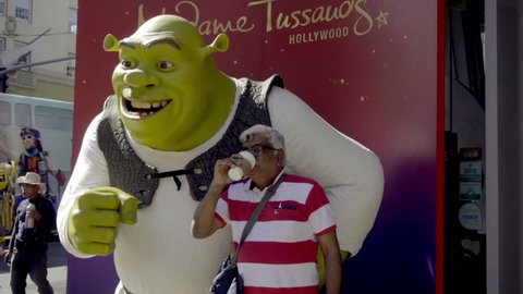 LOS ANGELES - OCT 23, 2016: Indian Man And Wife Posing With Shrek Statue On Hollywood Boulevard In LA CA. HW Blvd is a tourist attraction with many statues and actors dressed as film characters.