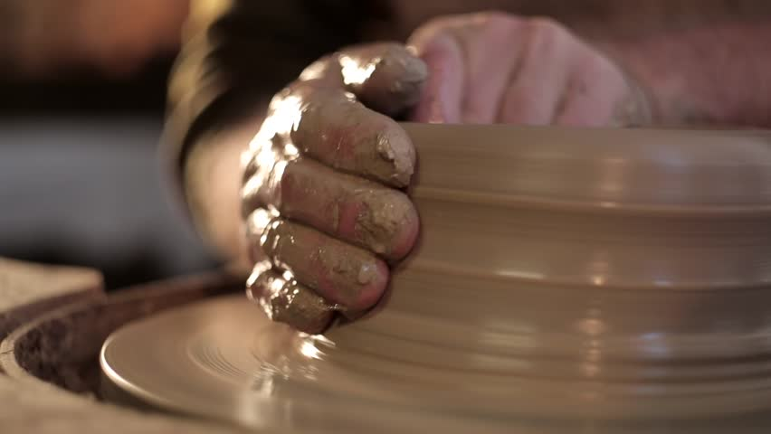 traditional pottery making, close up of potter's hands shaping a bowl on the spinning by clay