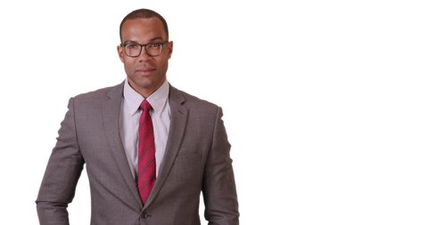 A black businessman poses for a portrait on a white background. An African American executive in a suit and tie stands looking at the camera on a blank backdrop. 4k