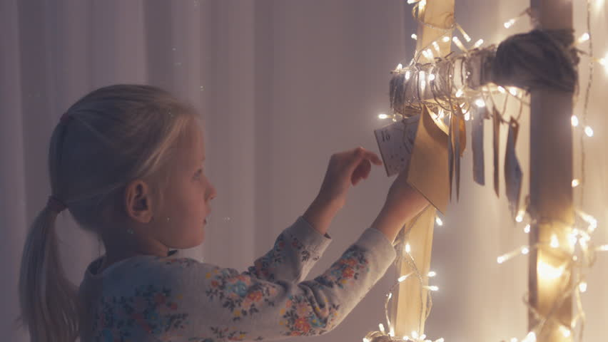 CU Little adorable girl unties the rope to get a daily envelope from a hand made advent calendar at her apartment. 4K UHD RAW edited footage, 60 fps slow motion