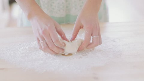 Girl by hands rolling dough for apple pie. Girl cooking apple pie at home with homemade prepared dough