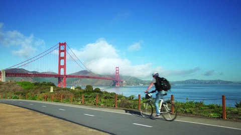 People ride bikes on road near Golden Gate Bridge and San Francisco bay 2