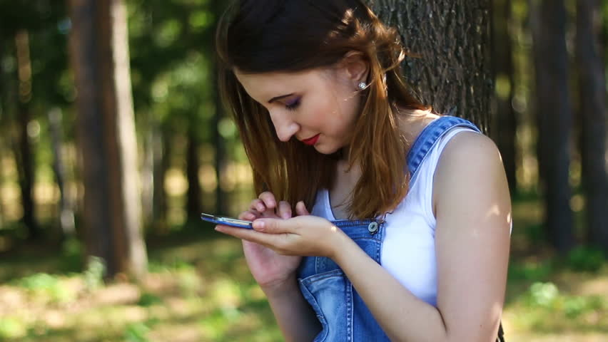 Woman uses a smartphone in the park   Shutterstock HD Video #22245790