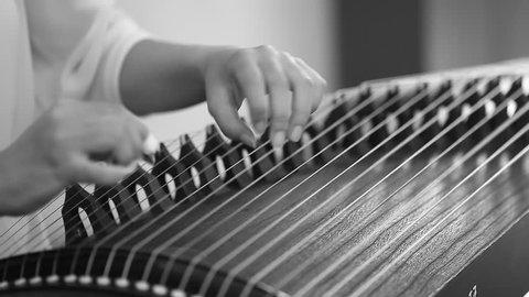 Hand of woman playing guzheng. Monochrome.
