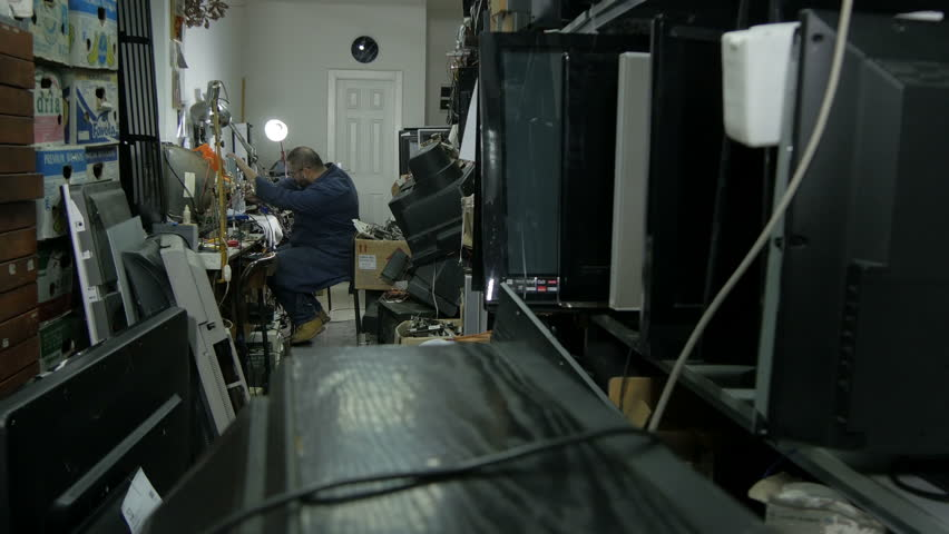 Repairman in blue work suit open broken television set in the crowded workshop with  broken plasma, LCD and old television devices, wide angle view, no color grading, raw video, interior scene.   Shutterstock HD Video #22270315