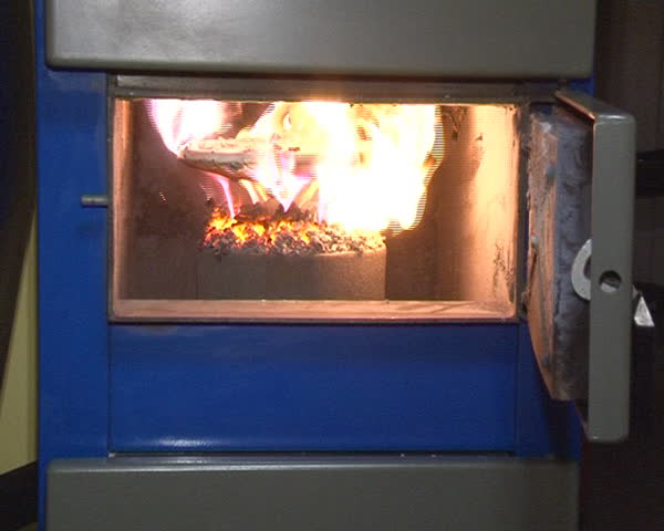 burning straw granules in boiler. flames and fire details. ecologic fuel use for house heating.