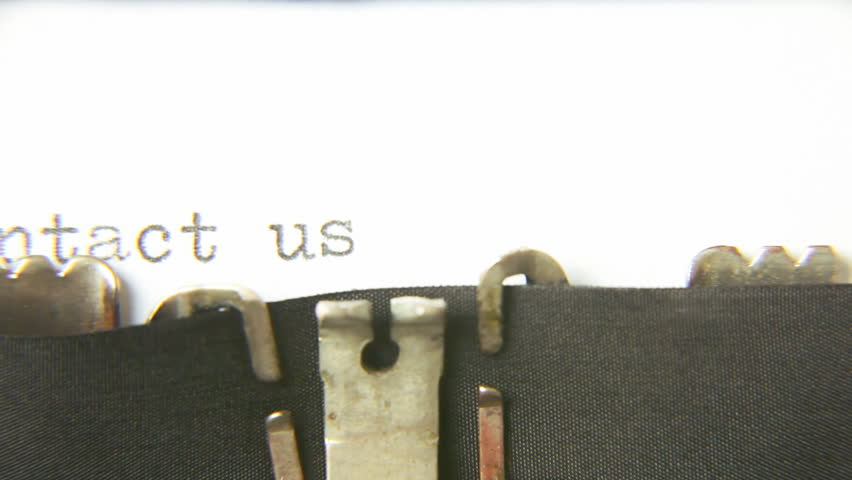 Typing the word Contact us - with an old vintage typewriter. Macro detail shot.
