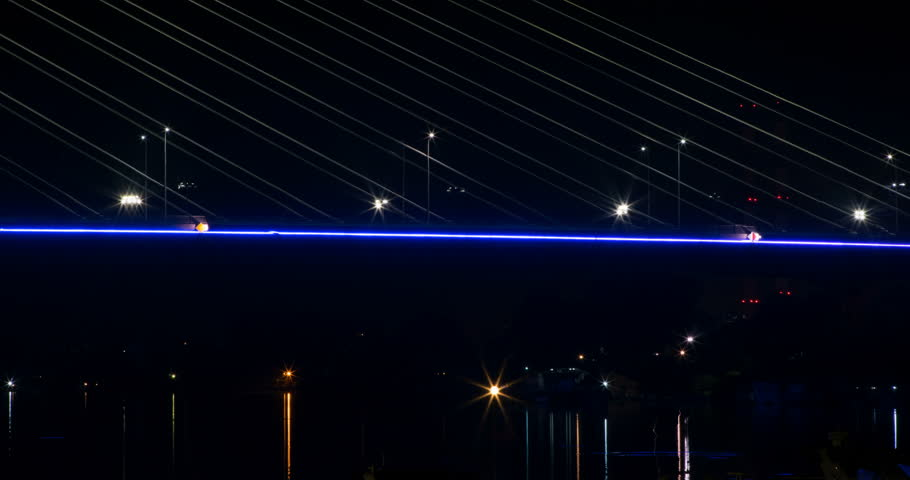 Night time lapse of a bridge, at night. Boats passing. Lights reflect on water #22330390